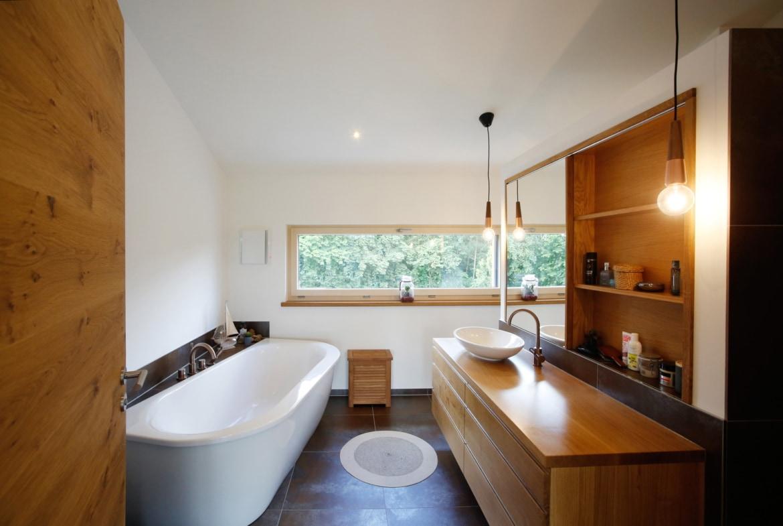 Badezimmer mit Badewanne & großem Waschtisch aus Holz - Haus Design innen modern Ideen Inneneinrichtung Baufritz ÖKOHAUS SCHELLENBERG - HausbauDirekt.de