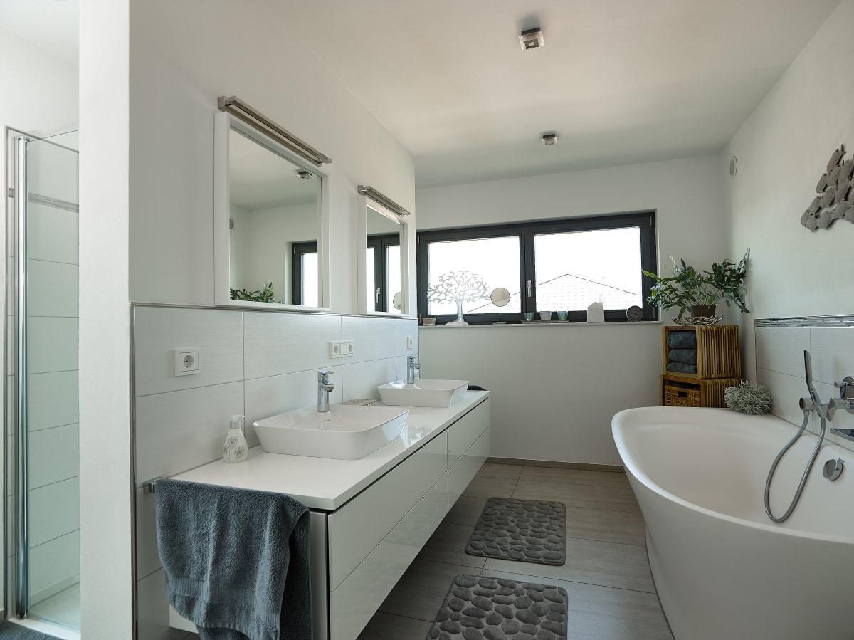 Badezimmer mit Raumteiler gemauert zwischen Doppelwaschbecken und Dusche - Ideen Einrichtung Fertighaus Bungalow Marmilla von GUSSEK HAUS - HausbauDirekt.de