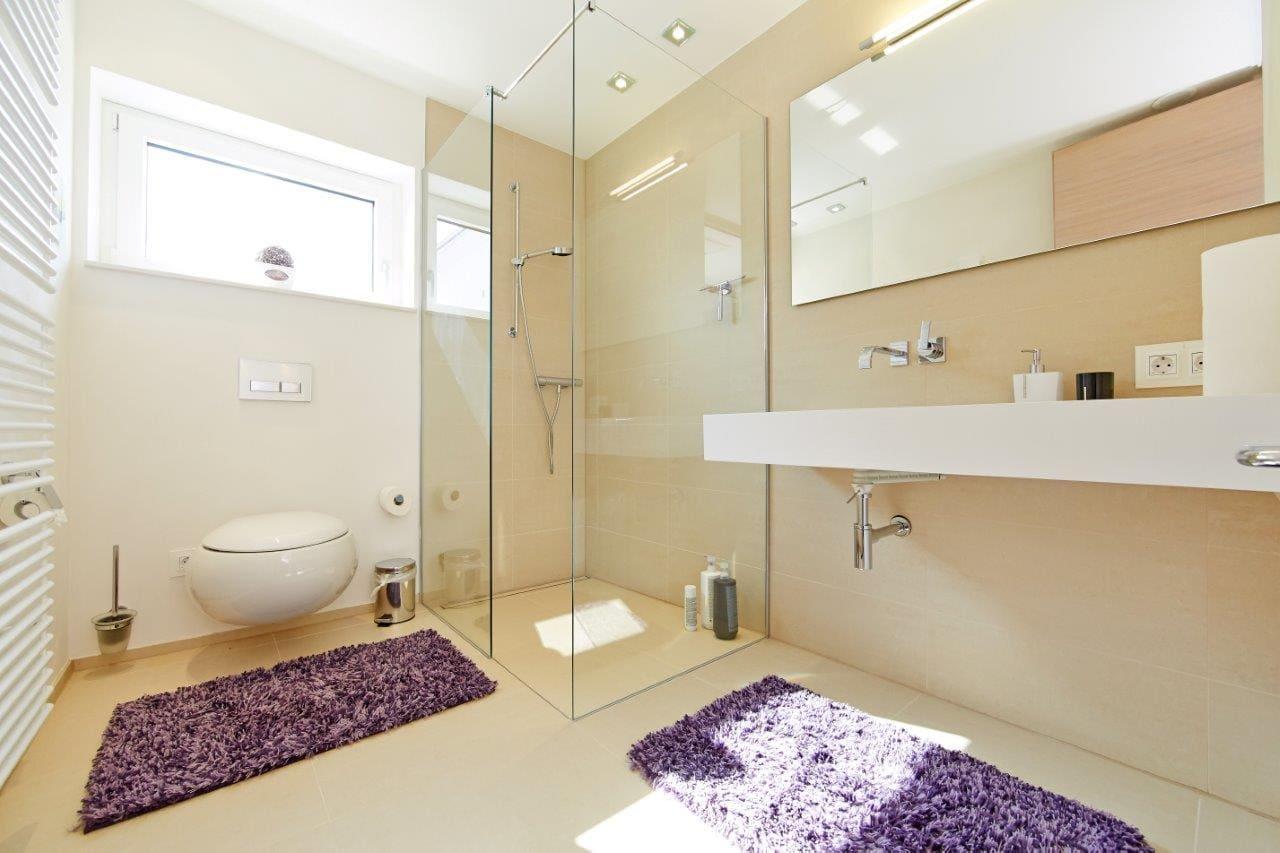 Badezimmer mit ebenerdiger Dusche - Inneneinrichtung Doppelhaushälfte Fertighaus Marseille von GUSSEK HAUS - HausbauDirekt.de
