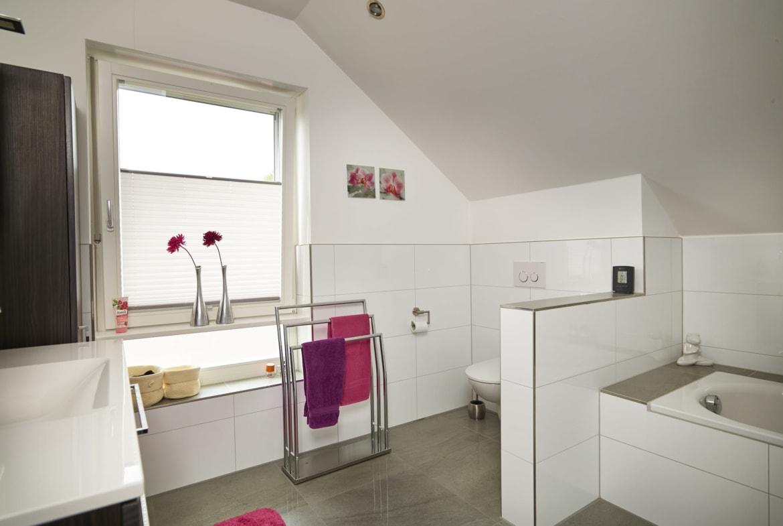 Badezimmer mit Dachschräge & Raumteiler zwischen WC und Badewanne halbhoch gemauert - Inneneinrichtung Ideen Einfamilienhaus Kastanienallee von GUSSEK HAUS - HausbauDirekt.de