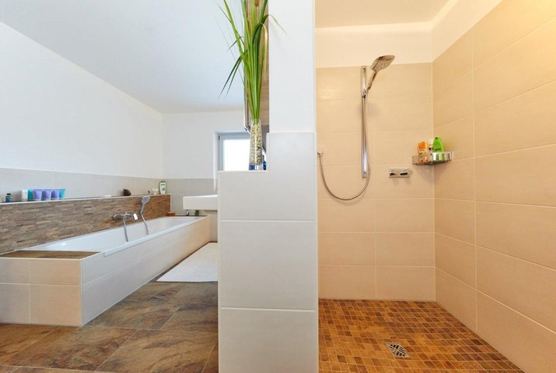 Badezimmer mit Badewanne & bodengleicher Dusche gemauert - Ideen Inneneinrichtung Fertighaus Hainbuchenallee von GUSSEK HAUS - HausbauDirekt.de