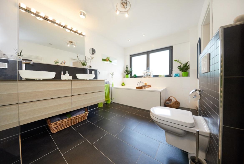 Badezimmer modern mit Doppelwaschbecken & Fliesen dunkel - Inneneinrichtung Fertighaus Parma von GUSSEK HAUS - HausbauDirekt.de