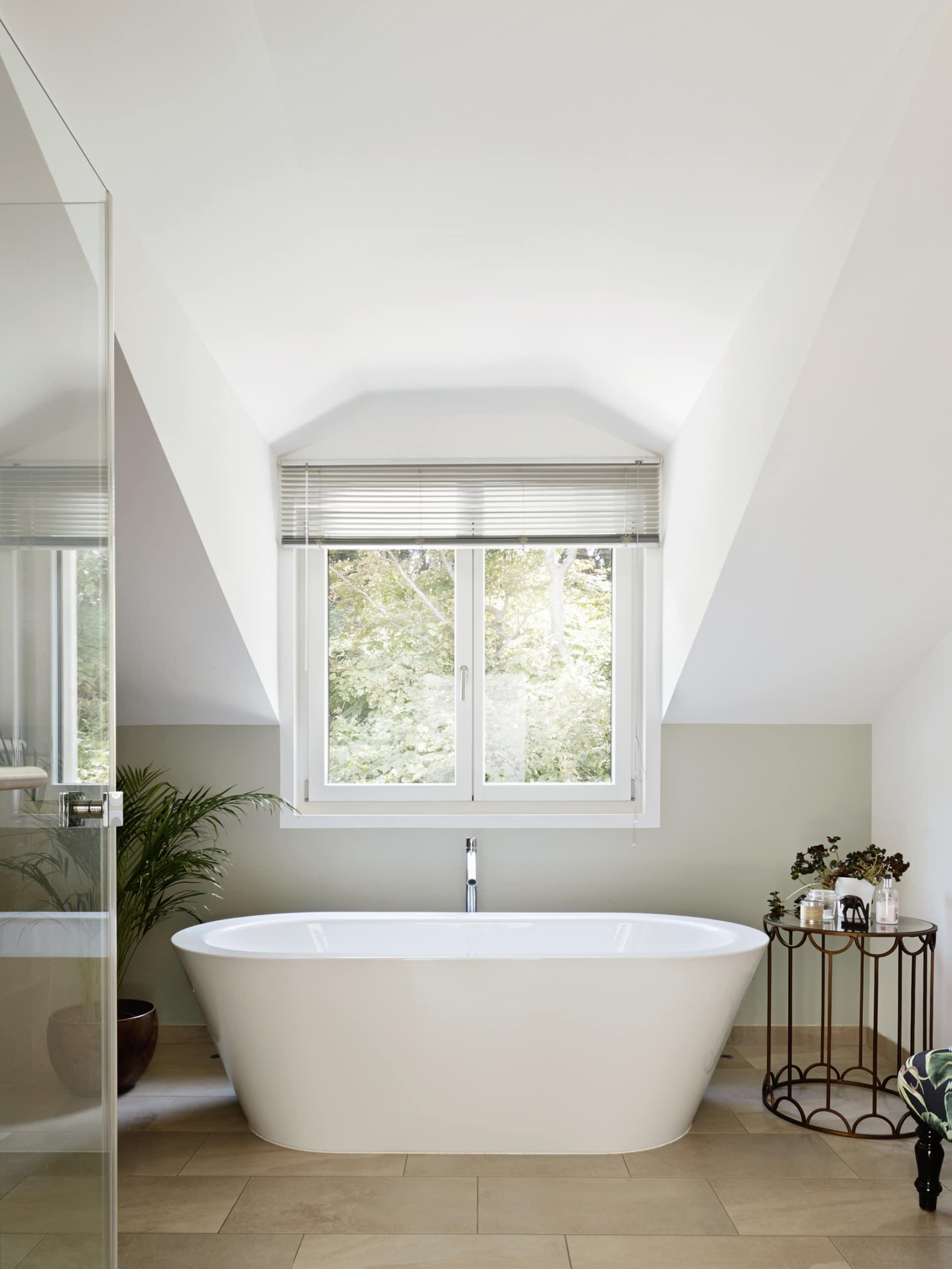 Badezimmer mit freistehender Badewanne unter Fenster - Inneneinrichtung Landhaus Villa Baufritz Fertighaus FORTESCUE - HausbauDirekt.de