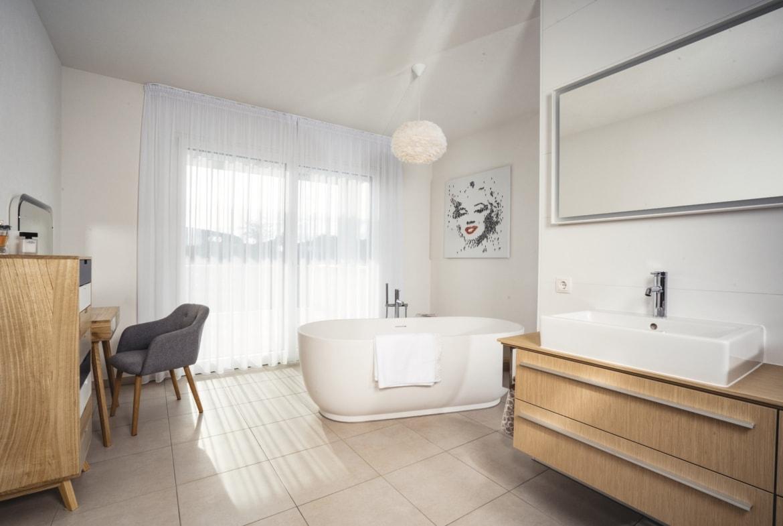 Badezimmer Inneneinrichtung modern mit freistehender Badewanne und Waschtisch - Haus Design Ideen innen Bauhaus Villa WeberHaus Fertighaus - HausbauDirekt.de