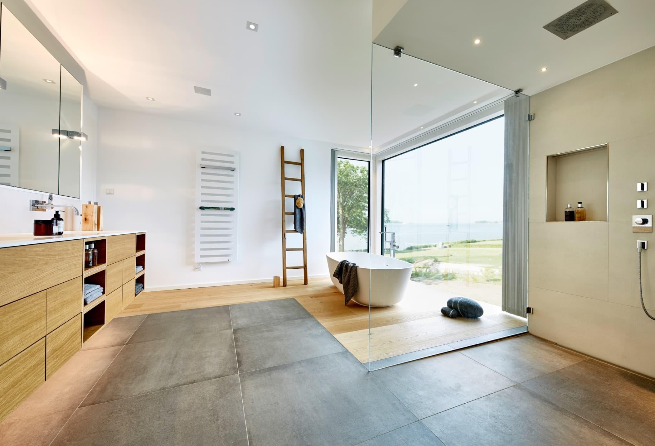 Luxuriöses Badezimmer mit bodengleicher Dusche & Badewanne freistehend - Ideen Interior Design Haus Inneneinrichtung BAUFRITZ Architektenhaus MEHRBLICK - HausbauDirekt.de
