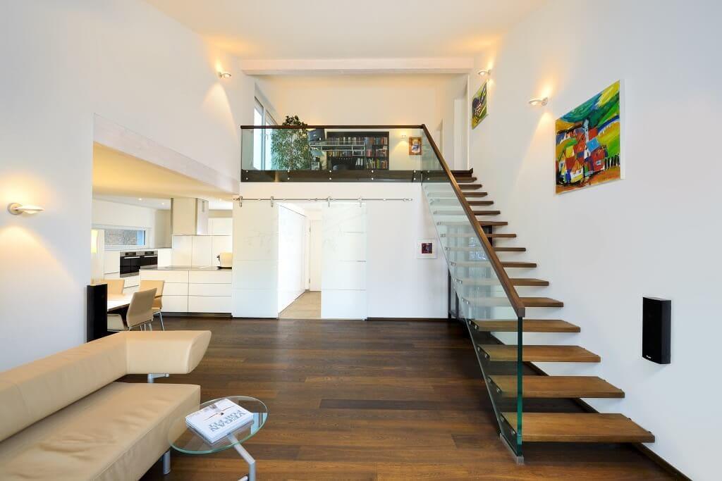 Fertighaus Bungalow innen modern mit Galerie & gerade Treppe mit Holz & Glasgeländer - Inneneinrichtung Haus Design Ideen Bungalow Ederer von Baufritz - HausbauDirekt.de