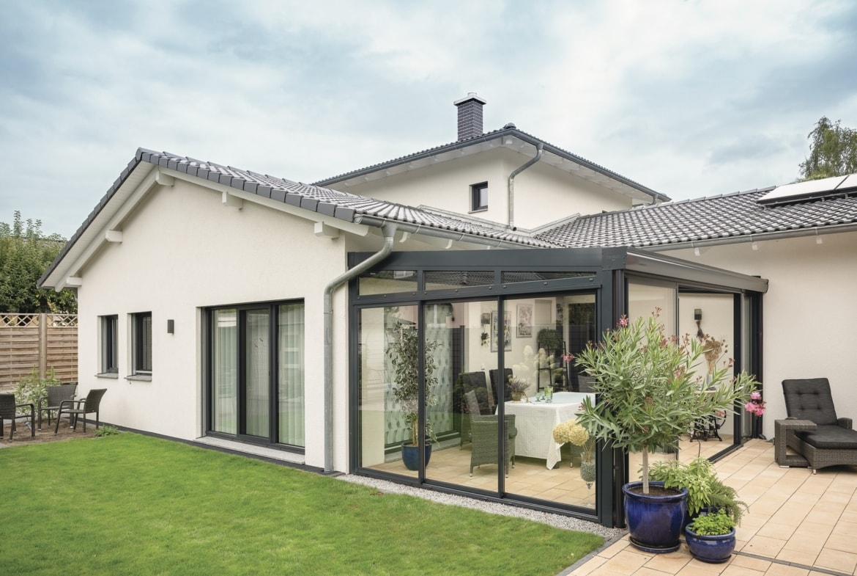 Landhaus Bungalow mediterran mit Satteldach und Wintergarten bauen - Haus Ideen Fertighaus WeberHaus Winkelbungalow - HausbauDirekt.de