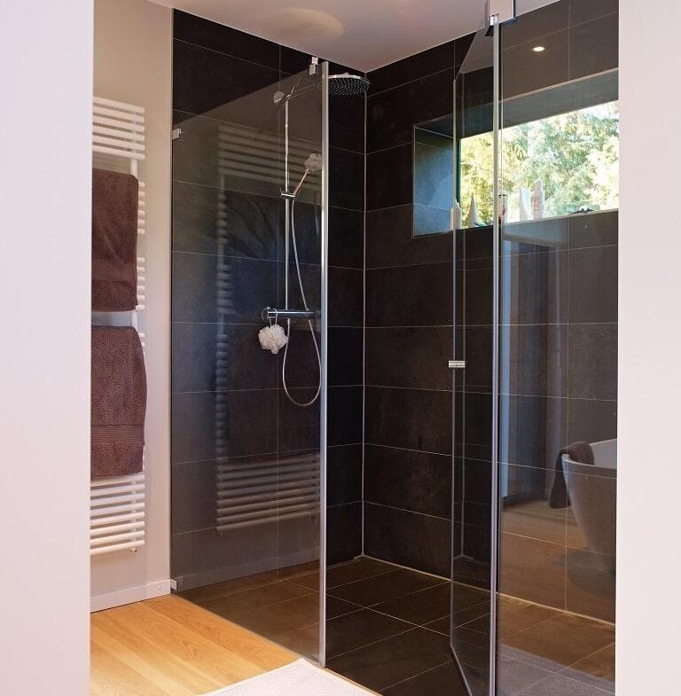 Ebenerdige Dusche modern, minimalistisch mit schwarzen Fliesen & Glaswand - Haus Design Ideen Inneneinrichtung Badezimmer Fertighaus Villa Crichton von Baufritz - HausbauDirekt.de