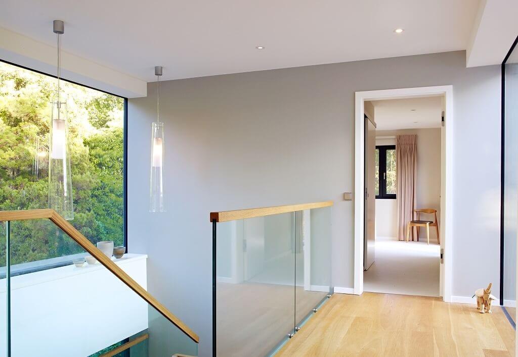 Flur mit Galerie & Treppengeländer aus Glas & Holz - Haus Design Ideen Inneneinrichtung Fertighaus Villa Crichton von Baufritz - HausbauDirekt.de