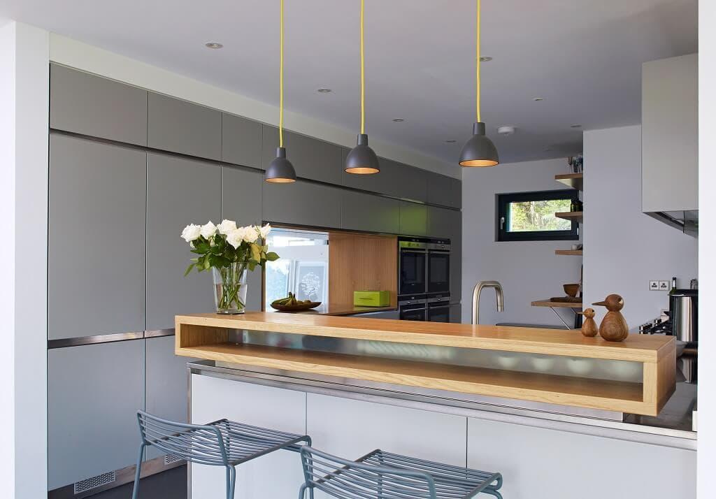 Moderne Küche minimalistisch mit Theke & Sitzgelegenheit in grau Holz weiss - Haus Design Ideen Inneneinrichtung Fertighaus Villa Crichton von Baufritz - HausbauDirekt.de