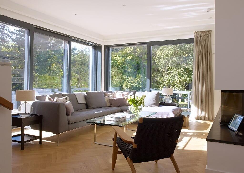 Modernes Wohnzimmer mit Kamin & bodentiefen Fenstern - Ideen Inneneinrichtung Luxus Design Haus Villa Crichton von Baufritz - HausbauDirekt.de