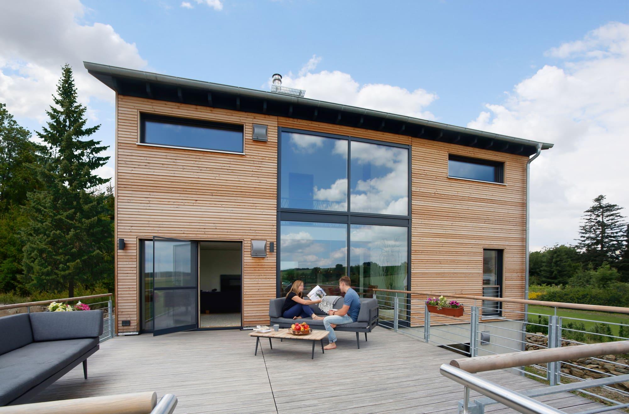 Modernes Holzhaus mit Galerie, Holz Fassade & großer Dachterrasse über Garage - Fertighaus bauen Ideen Baufritz Haus SCHELLENBERG - HausbauDirekt.de