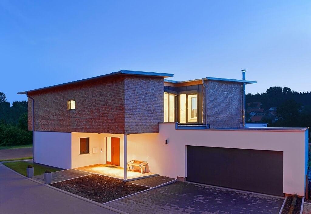 Einfamilienhaus modern mit Garage, Holz Fassade & Pultdach bauen - Fertighaus Designhaus Bullinger von Baufritz - HausbauDirekt.de