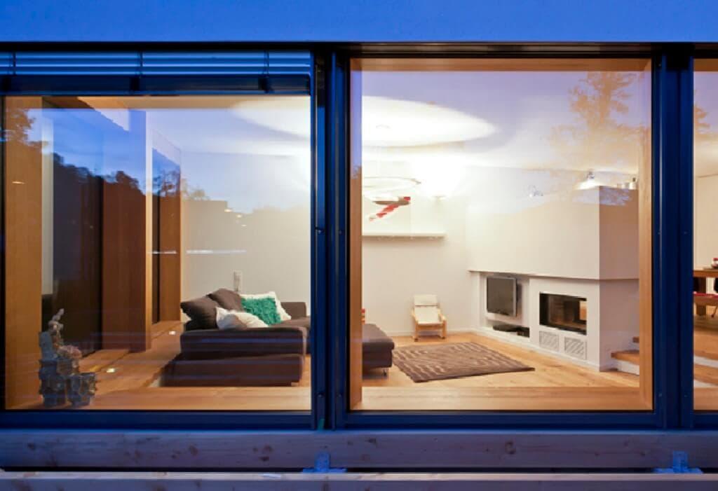 Einfamilienhaus modern Wohnzimmer mit Kamin & bodentiefe Fenster - Fertighaus Designhaus Bullinger von Baufritz - HausbauDirekt.de