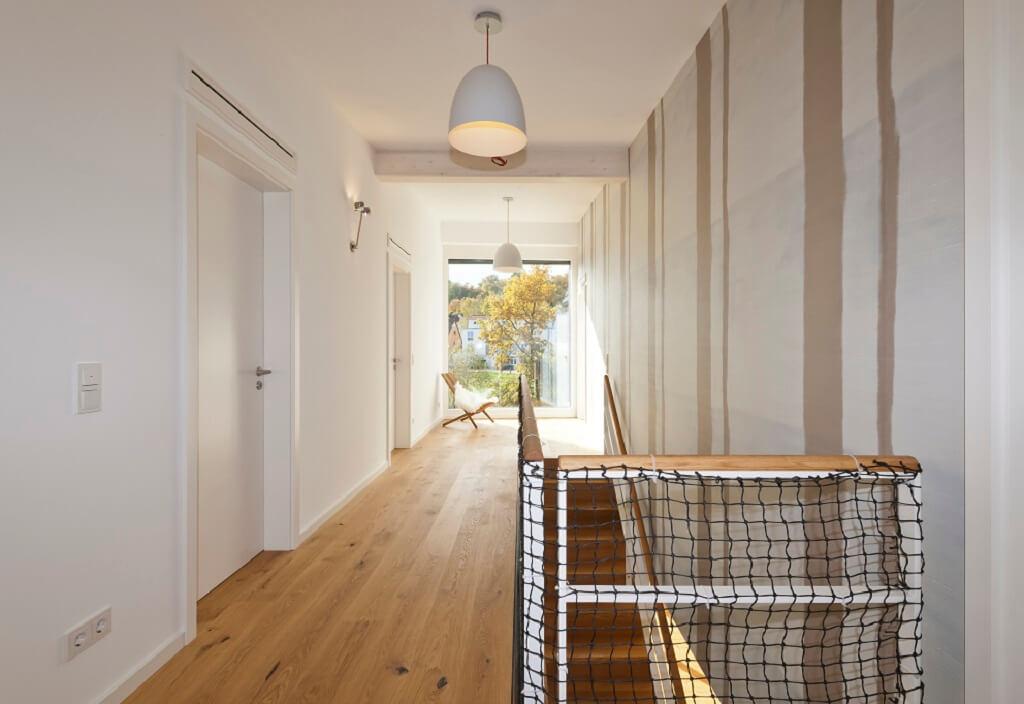 Flur mit Treppengeländer aus Netz - Haus Design Ideen innen, Einfamilienhaus Inneneinrichtung - Designhaus Bullinger von Baufritz - HausbauDirekt.de
