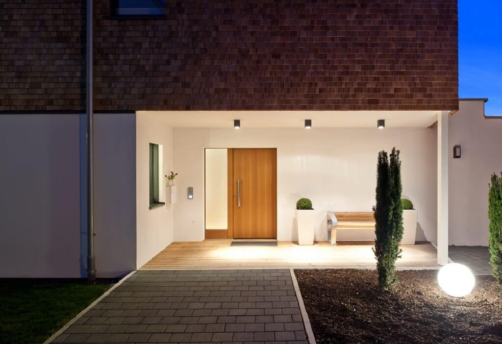 Einfamilienhaus modern mit überdachtem Eingang, Beleuchtung & Holz Putz Fassade - Fertighaus Designhaus Bullinger von Baufritz - HausbauDirekt.de