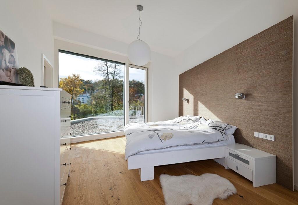Schlafzimmer modern weiss mit Wandgestaltung aus Holz - Haus Design Ideen innen, Einfamilienhaus Inneneinrichtung - Designhaus Bullinger von Baufritz - HausbauDirekt.de