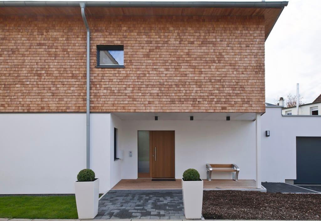 Einfamilienhaus modern mit überdachtem Hauseingang, Holz Fassade & Garage - Fertighaus Designhaus Bullinger von Baufritz - HausbauDirekt.de