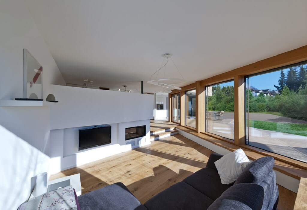 Offenes Wohnzimmer modern mit Kamin als Raumteiler - Haus Design Ideen innen, Einfamilienhaus Inneneinrichtung - Designhaus Bullinger von Baufritz - HausbauDirekt.de
