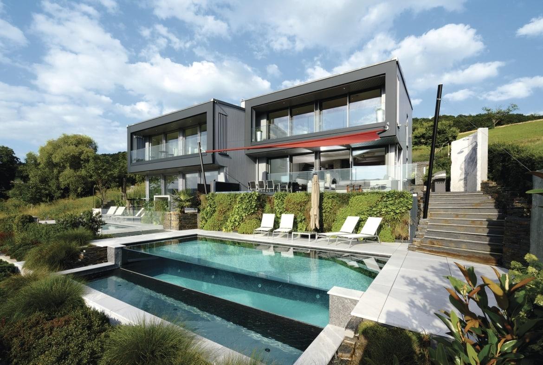 Doppelhaus Villa modern am Hang mit Flachdach und Pool Terrasse im Bauhausstil bauen - WeberHaus Fertighaus - HausbauDirekt.de
