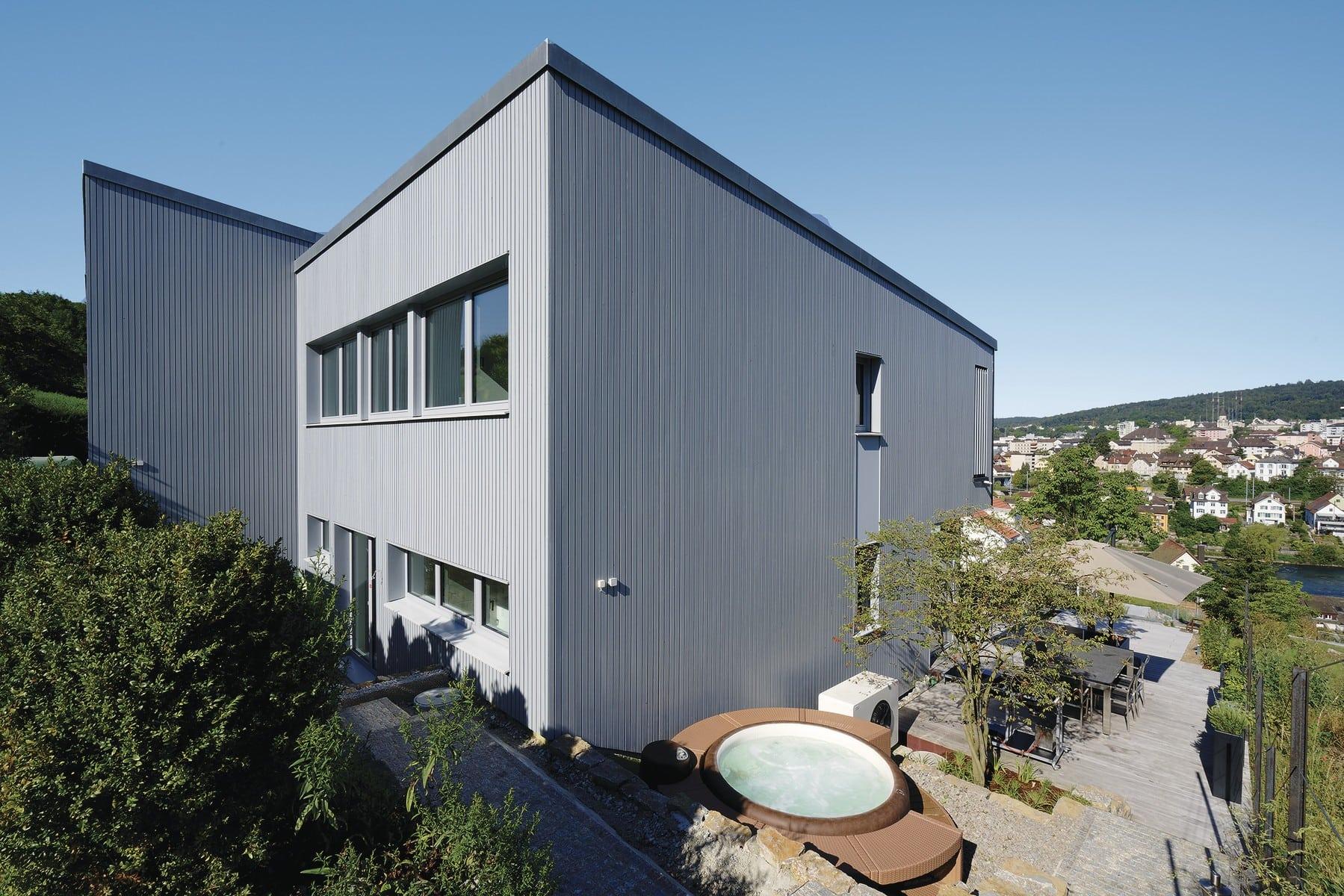 Doppelhaus modern am Hang mit Flachdach und Holz Fassade in Grau bauen - WeberHaus Fertighaus - HausbauDirekt.de