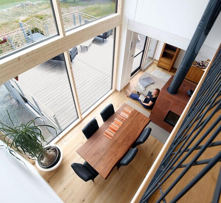 Essbereich mit Kaminofen & Galerie über 2 Etagen - Haus Design innen modern Ideen Inneneinrichtung Baufritz ÖKOHAUS SCHELLENBERG - HausbauDirekt.de