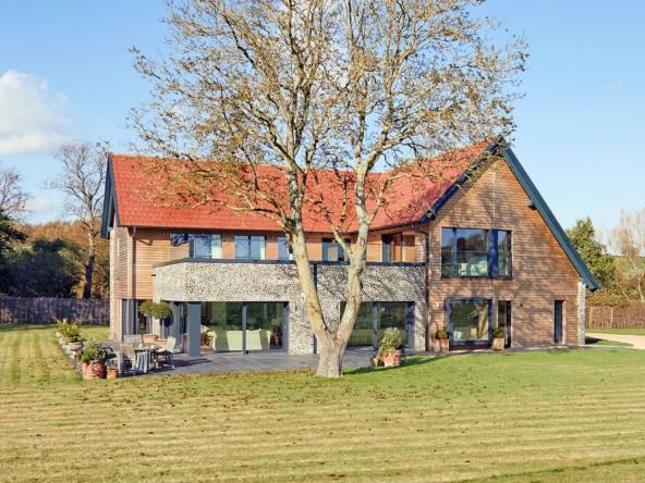 Modernes Einfamilienhaus im Landhausstil mit Satteldach und Holz Fassade bauen - Haus Ideen Fertighaus Baufritz Landhaus LLOYD WEBBER - HausbauDirekt.de