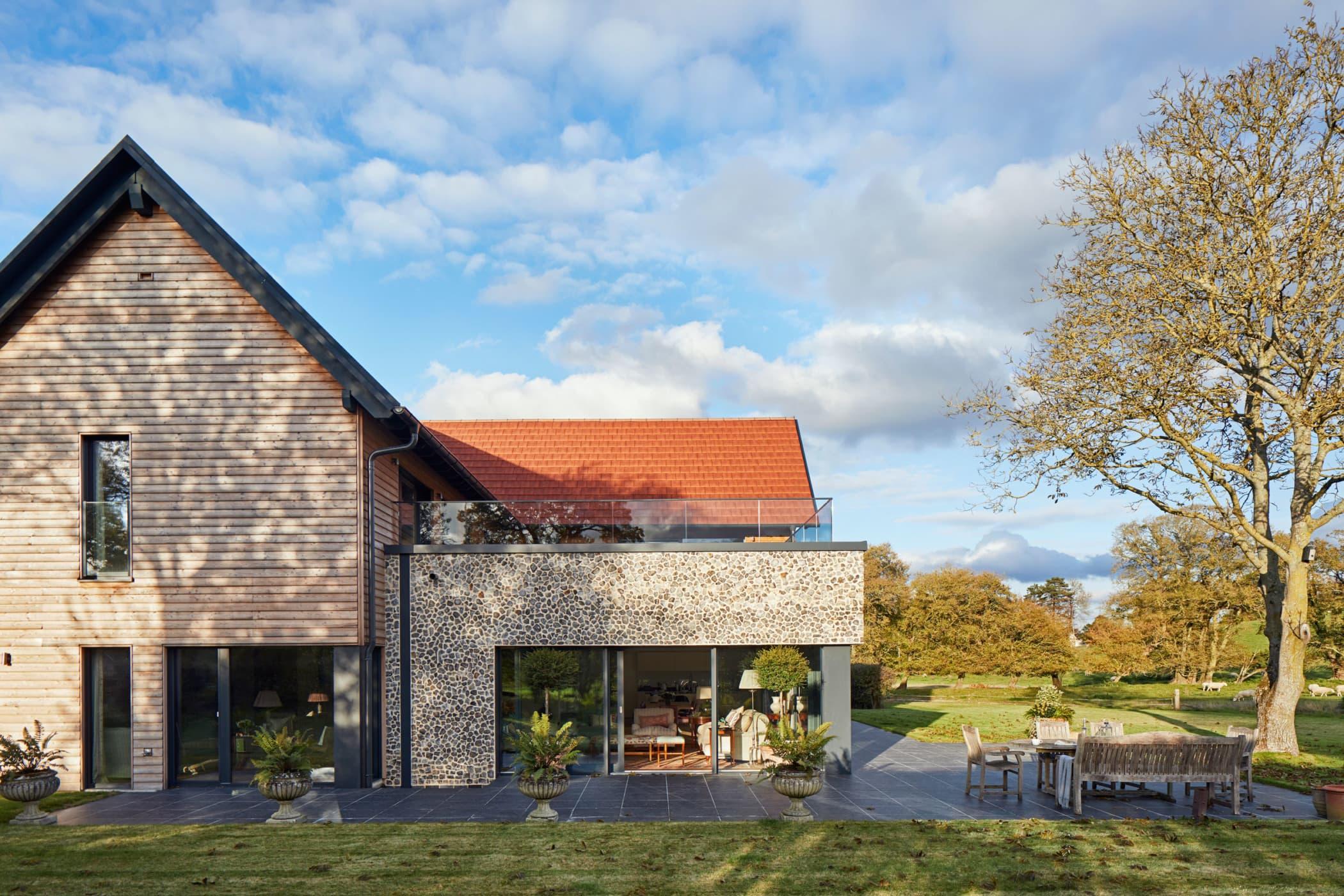 Modernes Einfamilienhaus im Landhausstil mit Satteldach und Erker mit Dachterrasse bauen - Haus Ideen Fertighaus Baufritz Landhaus LLOYD WEBBER - HausbauDirekt.de