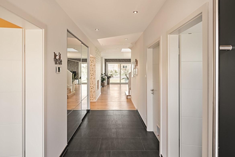 Flur modern mit dunklem Holz Boden - Haus Design Ideen innen Einfamilienhaus Inneneinrichtung Fertighaus Lichtdurchfluteter Kubus von WeberHaus - HausbauDirekt.de