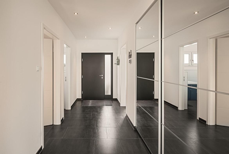 Flur & Hauseingang modern mit Spiegelschrank & Fliesen - Haus Design Ideen innen Einfamilienhaus Inneneinrichtung Fertighaus Lichtdurchfluteter Kubus von WeberHaus - HausbauDirekt.de