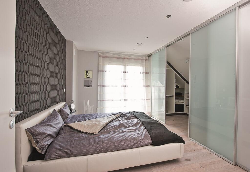 Schlafzimmer modern mit Ankleide unter Dachschräge - Inneneinrichtung Haus bauen Design Ideen innen WeberHaus Fertighaus Generation 5.5 Haus 300 - HausbauDirekt.de
