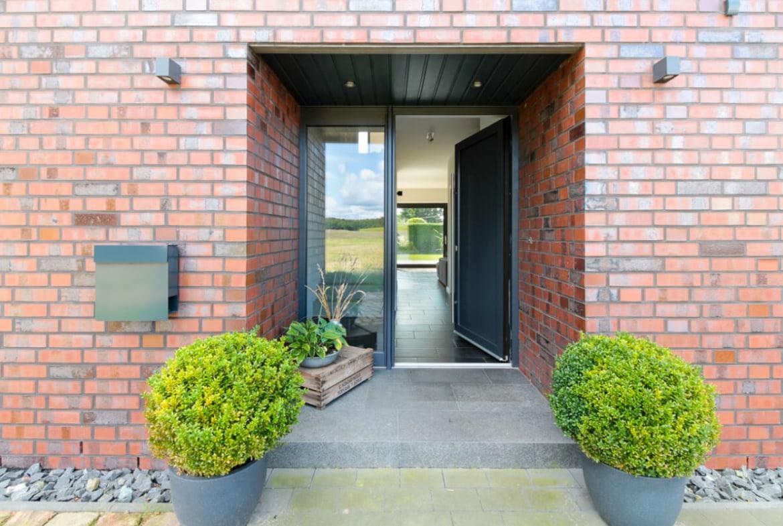 Überdachter Hauseingang mit Stufe & Haustür mit Fenster - Architektur Detail Haus Design Ideen Massivhaus Vario-Haus 160 von ECO System HAUS - HausbauDirekt.de