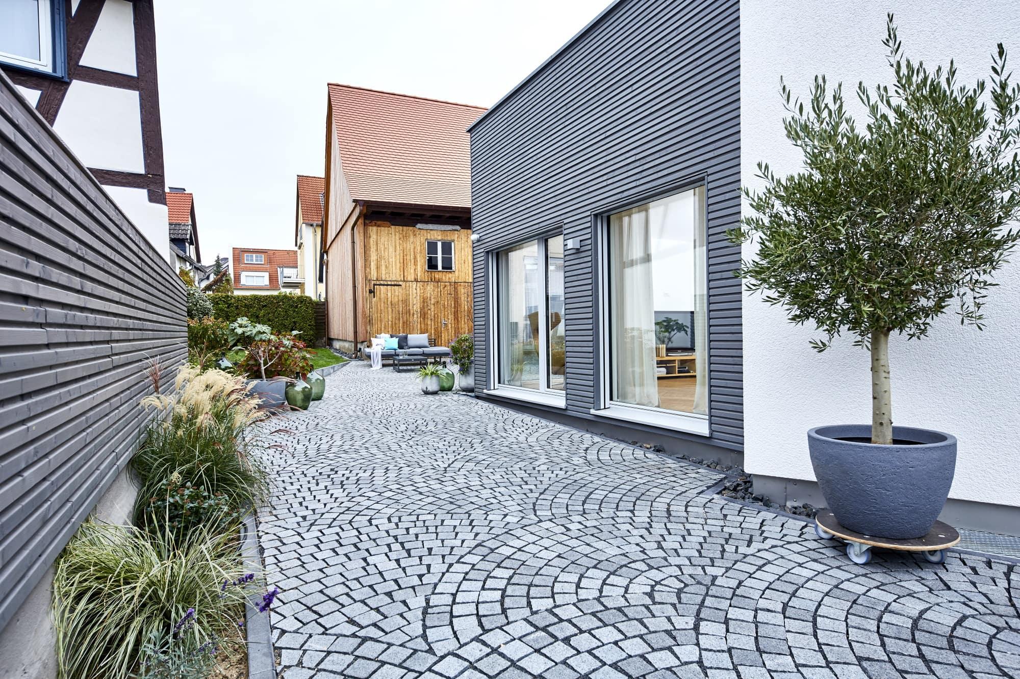Moderner Erker Anbau mit Holz Fassade & Innenhof gepflastert - Fertighaus bauen Ideen ökologisches Baufritz Haus STADTHAUS EHRMANN - HausbauDirekt.de