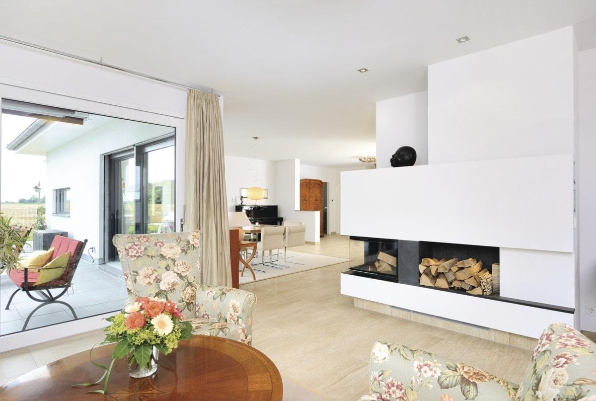 Fertighaus Bungalow innen mit Kamin als Raumteiler - Haus ebenerdig bauen Ideen WeberHaus Winkelbungalow in zeitlosem Design - HausbauDirekt.de