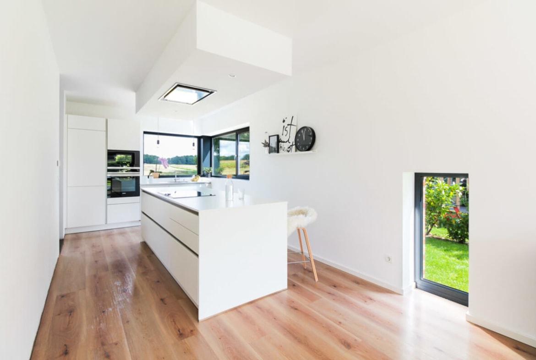 Offene Küche modern minimalistisch weiss mit Kochinsel - Inneneinrichtung Haus Design Ideen innen Massivhaus Vario-Haus 160 von ECO System HAUS - HausbauDirekt.de