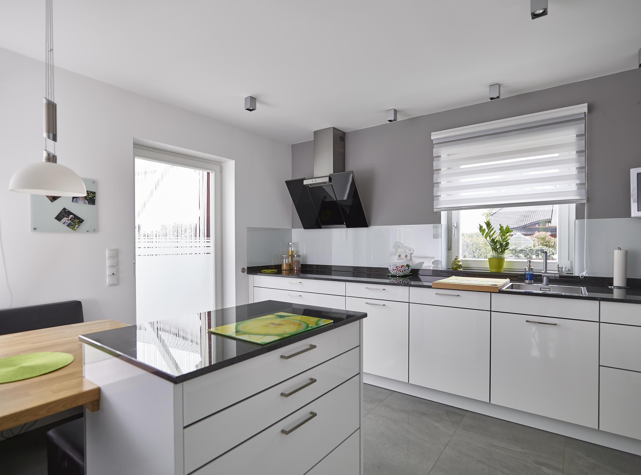 Küche modern weiß mit Insel & Tisch - Inneneinrichtung Ideen Einfamilienhaus Kastanienallee von GUSSEK HAUS - HausbauDirekt.de