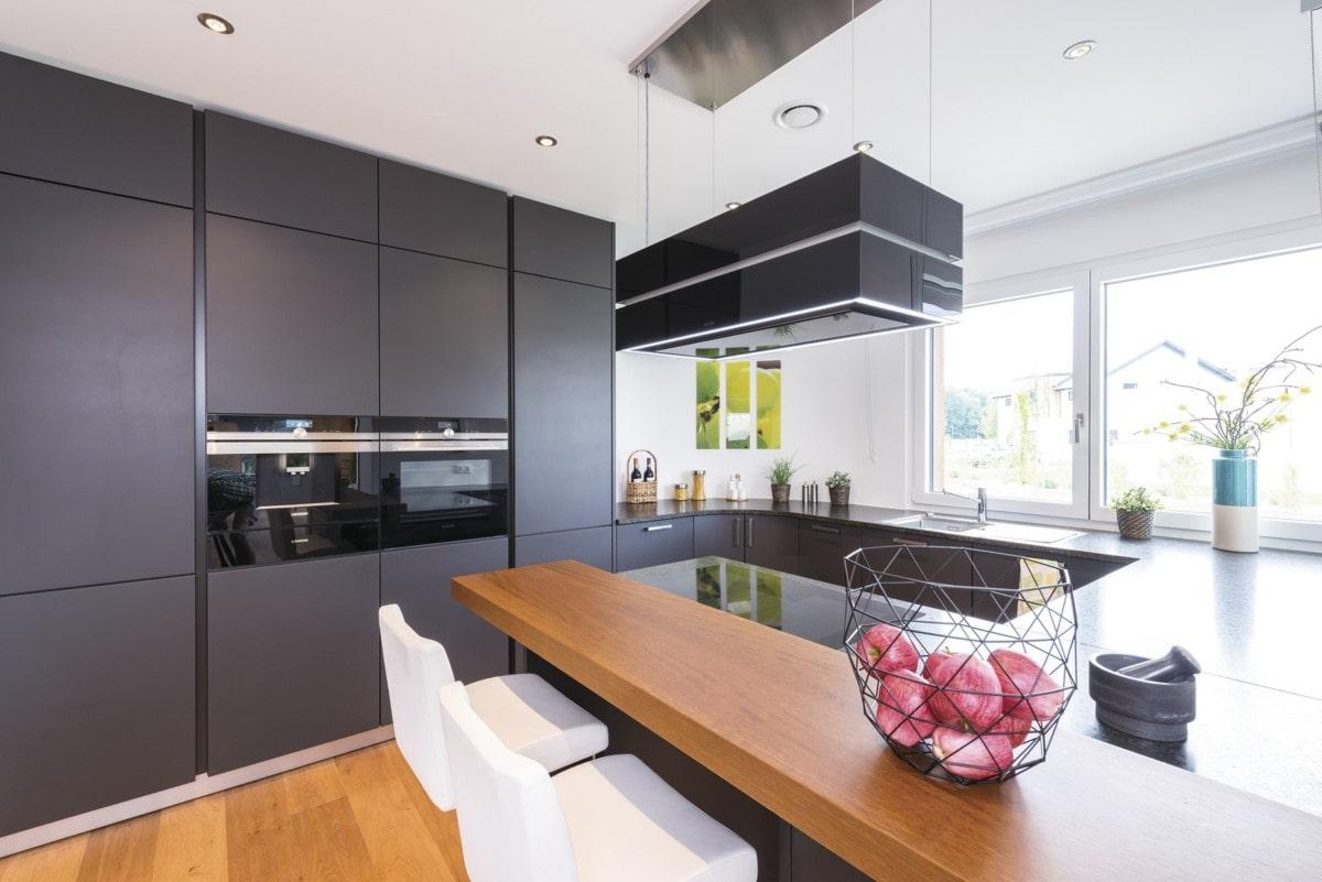 Offene Küche mit Theke grau weiß Holz - Inneneinrichtung Ideen WeberHaus Stadtvilla Guenzburg - HausbauDirekt.de