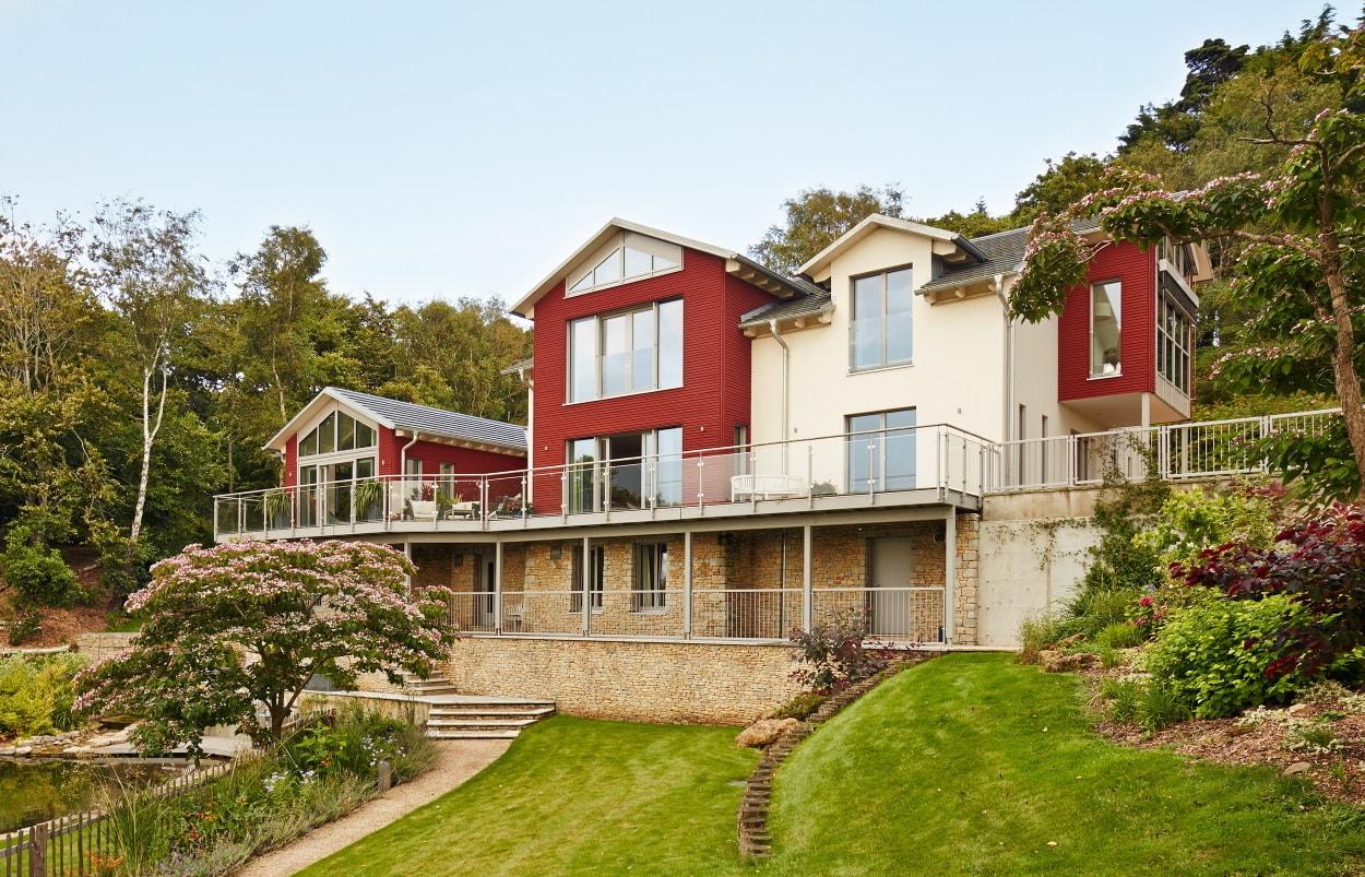 Landhaus Villa am Hang mit Holz Putz Fassade & Satteldach Architektur - Haus bauen Ideen Baufritz Fertighaus Villa FORTESCUE - HausbauDirekt.de