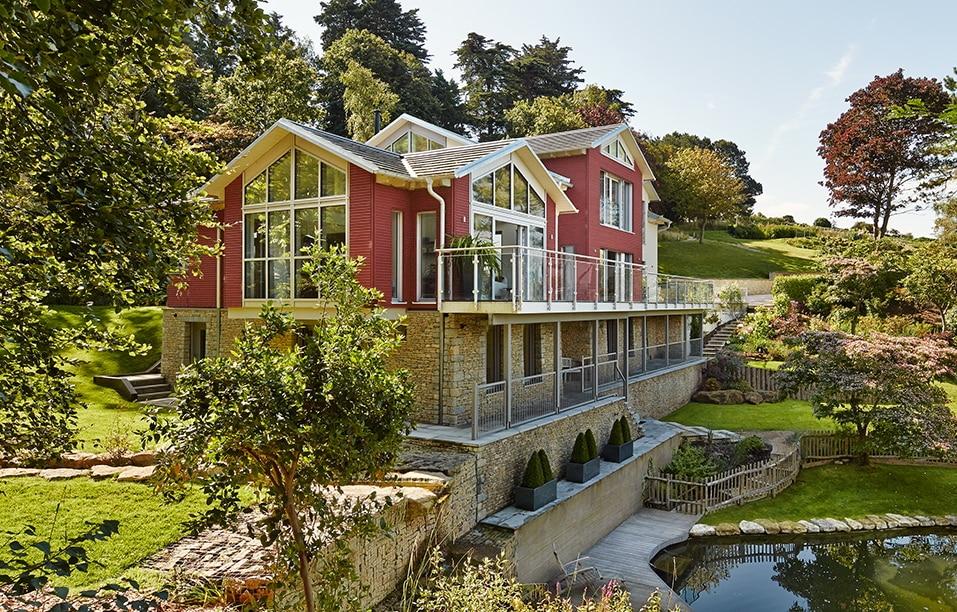 Luxus Landhaus Villa in Hanglage mit Holz Fassade & Satteldach Architektur - Haus bauen Ideen Baufritz Fertighaus Villa FORTESCUE - HausbauDirekt.de