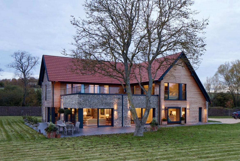 Einfamilienhaus modern im Landhausstil mit Satteldach und Holz Fassade bauen - Haus Ideen Fertighaus Baufritz Landhaus LLOYD WEBBER - HausbauDirekt.de