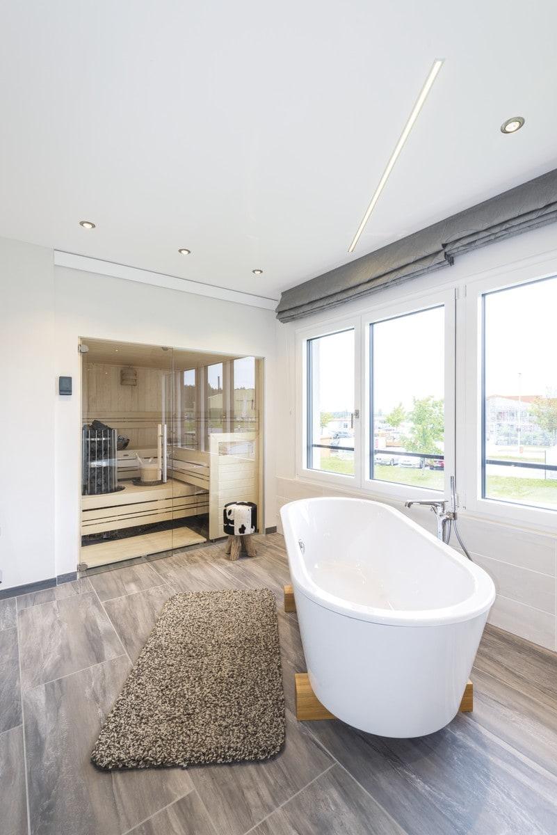 Luxus Badezimmer mit Sauna, freistehender Badewanne & Fliesen in Holzoptik - Inneneinrichtung Ideen WeberHaus Stadtvilla Guenzburg - HausbauDirekt.de