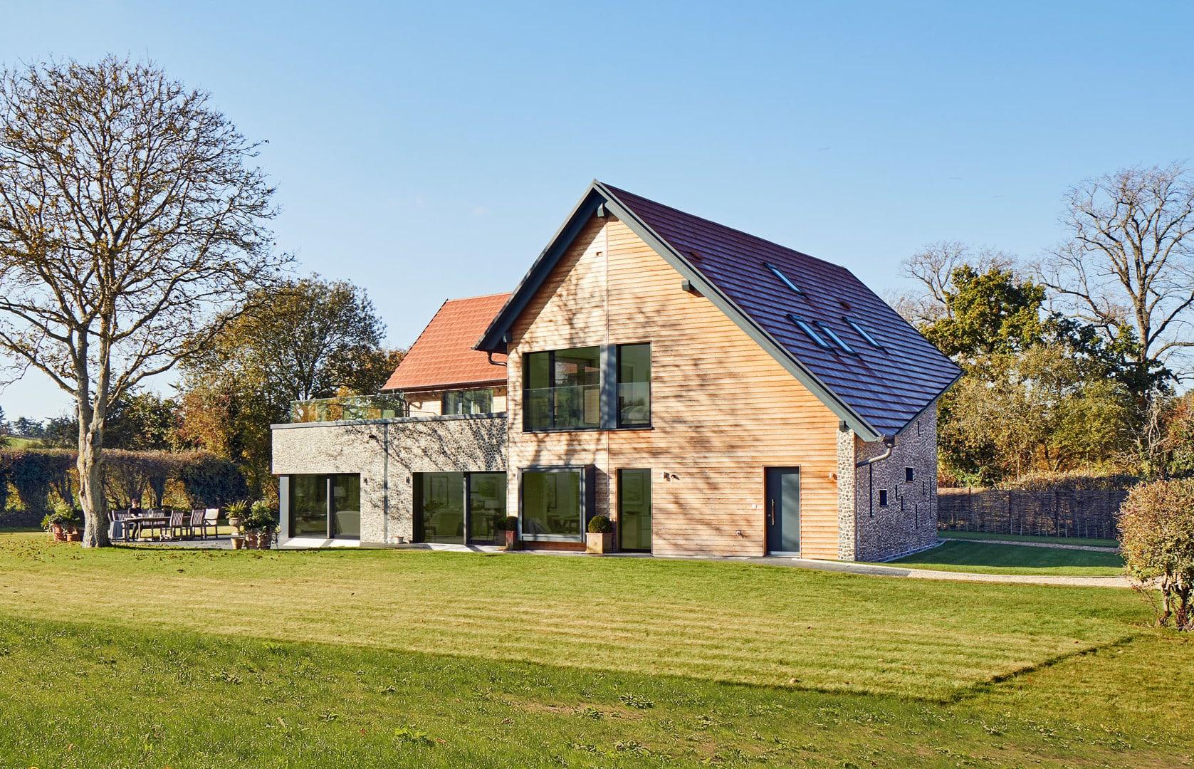 Modernes Holzhaus mit Satteldach und Holz Fassade bauen -Einfamilienhaus Ideen Fertighaus Baufritz Landhaus LLOYD WEBBER - HausbauDirekt.de