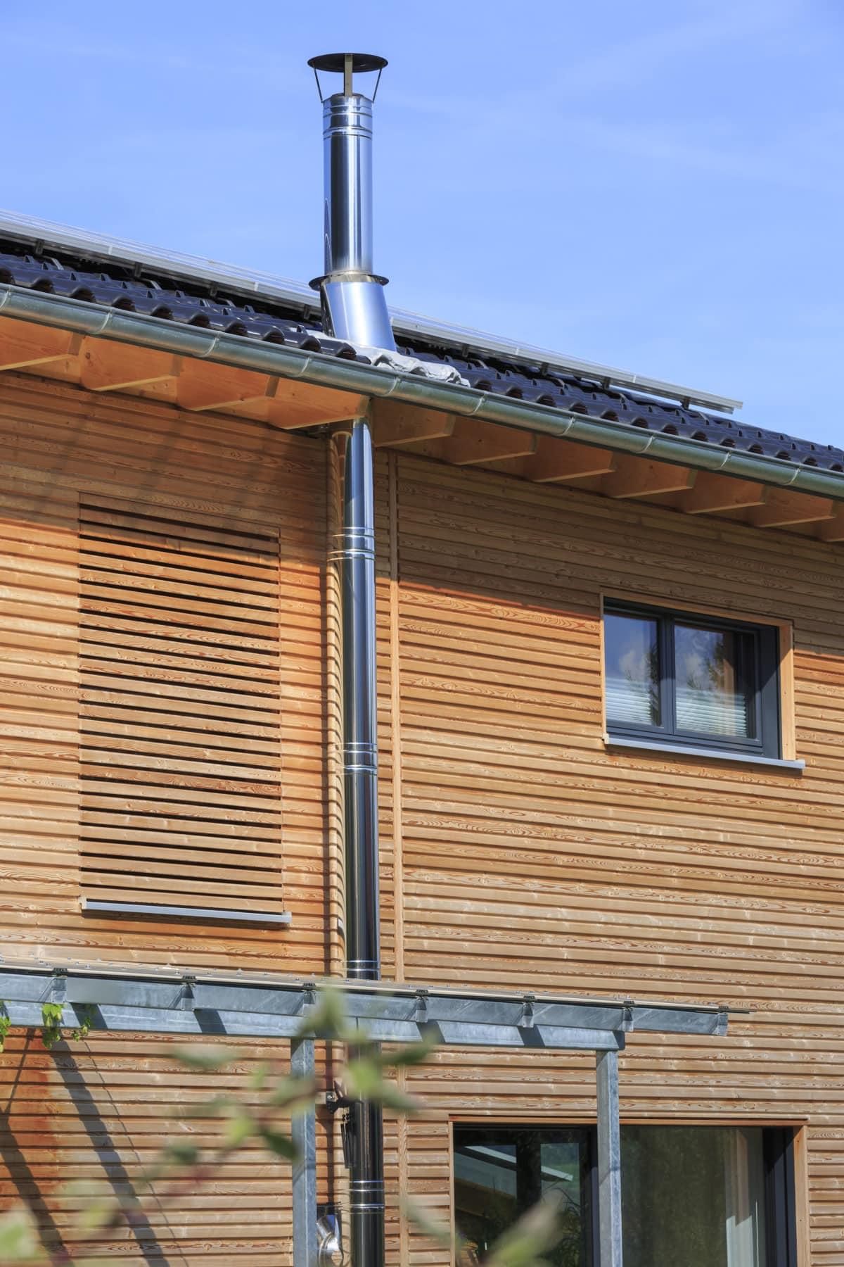 Holz Fassade mit Aussenkamin & Pergola - Architektur Detail Haus Design Ideen Fertighaus Ökohaus Schneider / Baufritz - HausbauDirekt.de
