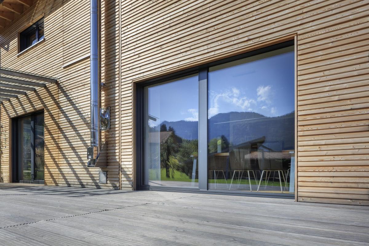 Holz Fassade, bodentiefe Fenster & Terrasse mit Holzbelag - Haus Design Ideen Fertighaus Ökohaus Schneider / Baufritz - HausbauDirekt.de