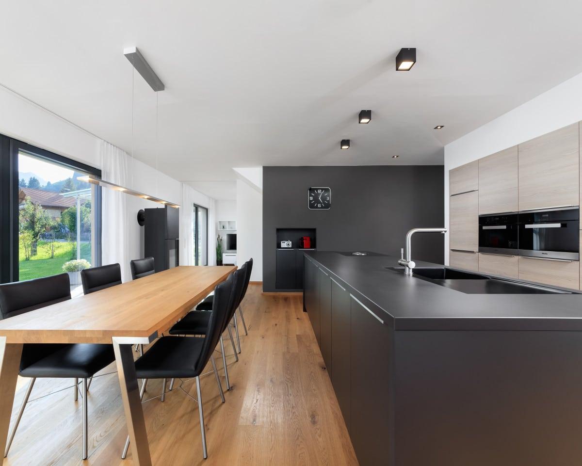 Küche modern offen mit Kochinsel grau & Esstisch aus Holz - Inneneinrichtung Haus Design Ideen innen Fertighaus Ökohaus Schneider / Baufritz - HausbauDirekt.de