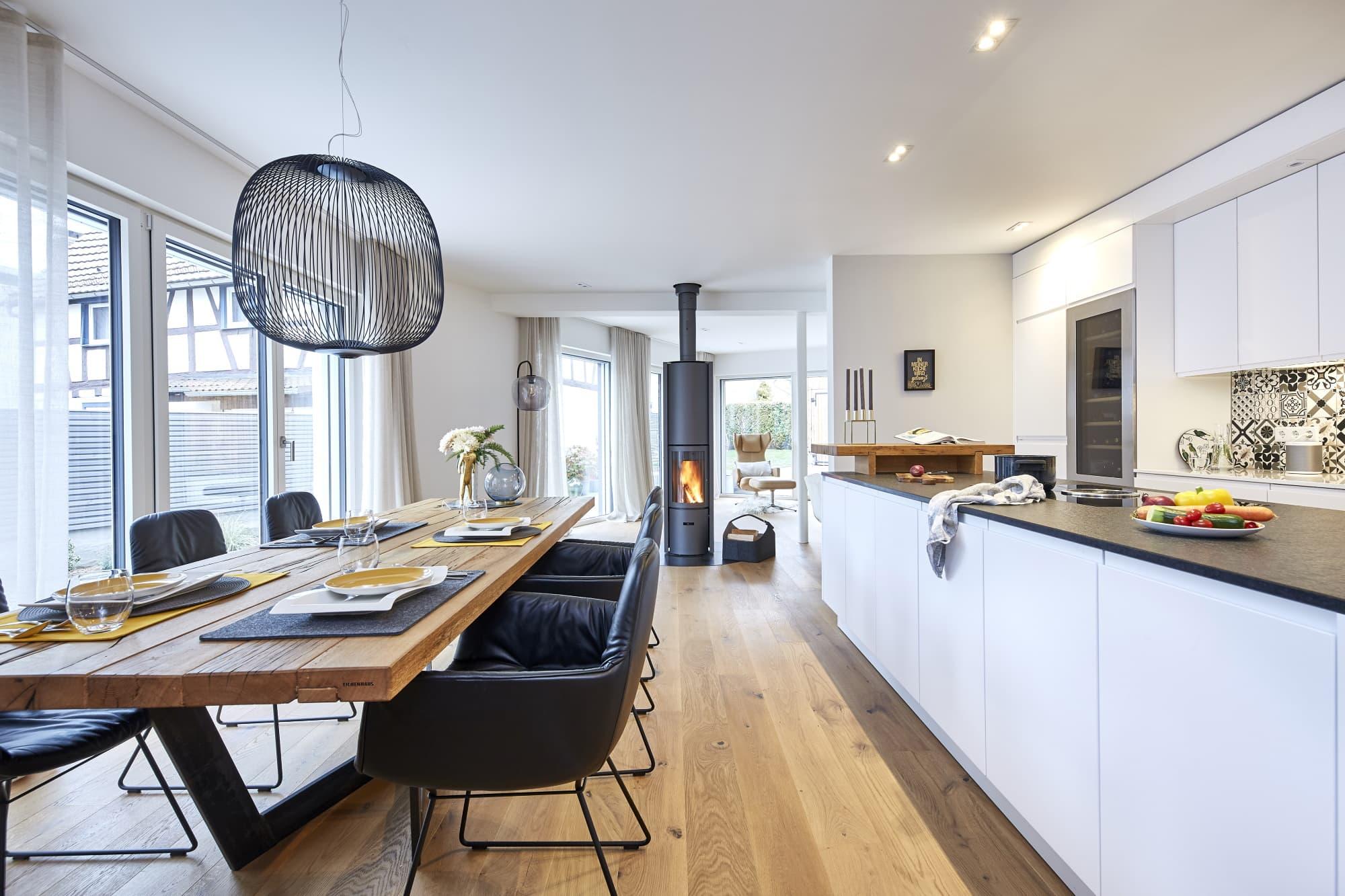 Offene Küche modern weiß mit großem Esstisch rustikal aus Holz & Kaminofen als Raumteiler - Ideen Inneneinrichtung Haus Design Baufritz STADTHAUS EHRMANN - HausbauDirekt.de