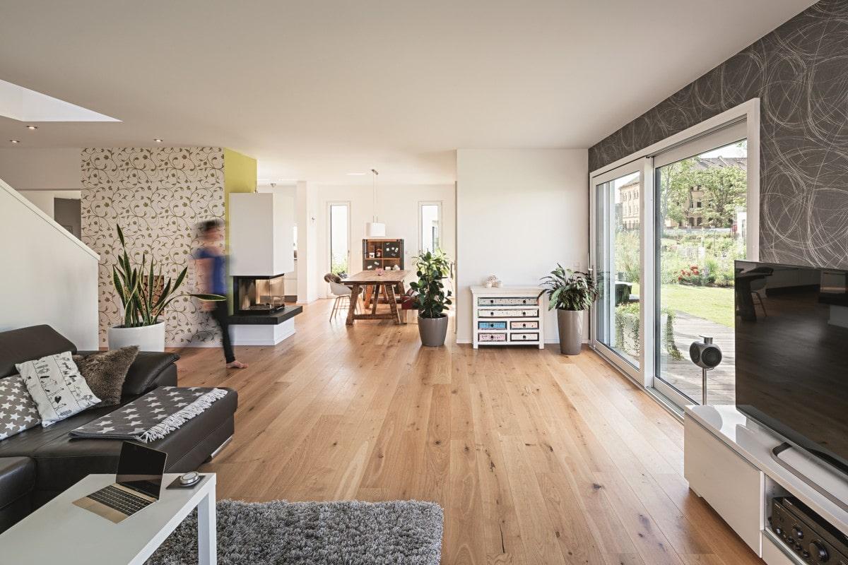 Offenes Wohn-Esszimmer modern mit Kamin als Raumteiler - Haus Design Ideen innen Einfamilienhaus Fertighaus Lichtdurchfluteter Kubus von WeberHaus - HausbauDirekt.de