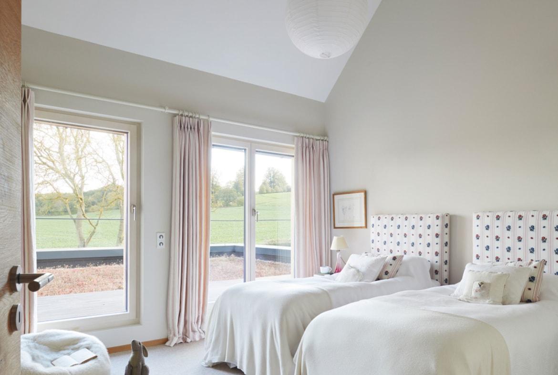 Schlafzimmer mit Dachschräge - Inneneinrichtung Haus Design Ideen innen Baufritz Landhaus LLOYD WEBBER - HausbauDirekt.de