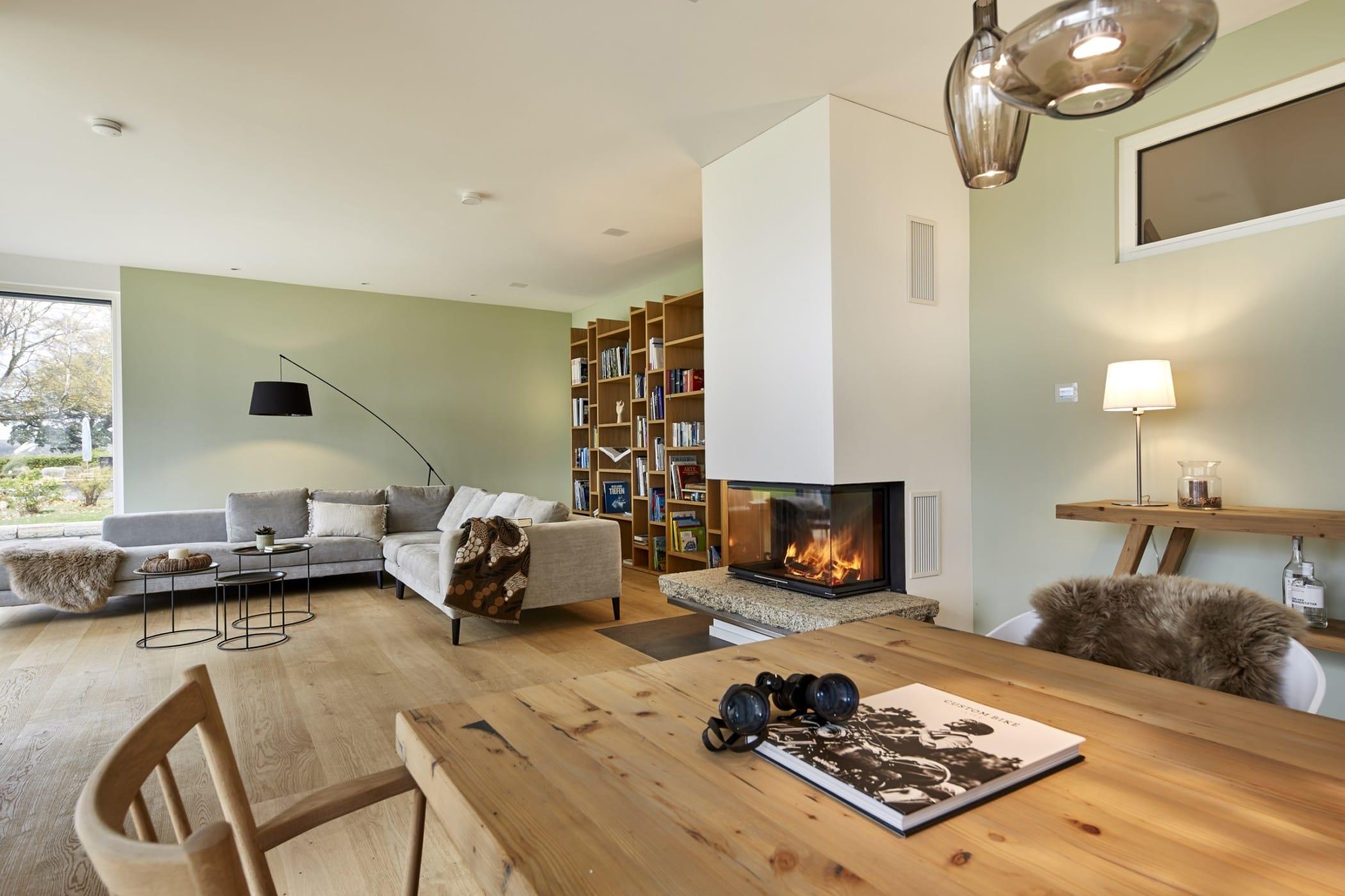 Offenes Wohnzimmer modern mit Essbereich & Kamin - Wohnideen Haus Inneneinrichtung BAUFRITZ Architektenhaus MEHRBLICK - HausbauDirekt.de