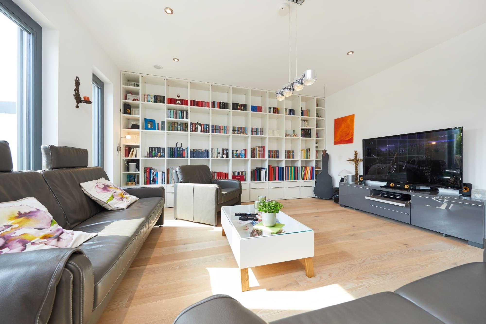 Wohnzimmer modern mit TV Board grau & Bücherregal - Ideen Inneneinrichtung Doppelhaushälfte Monza von GUSSEK HAUS - HausbauDirekt.de
